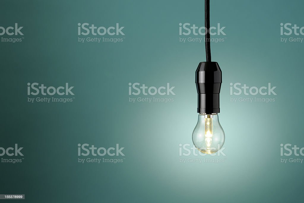 Illuminated LED light bulb against blue background with copy space royalty-free stock photo