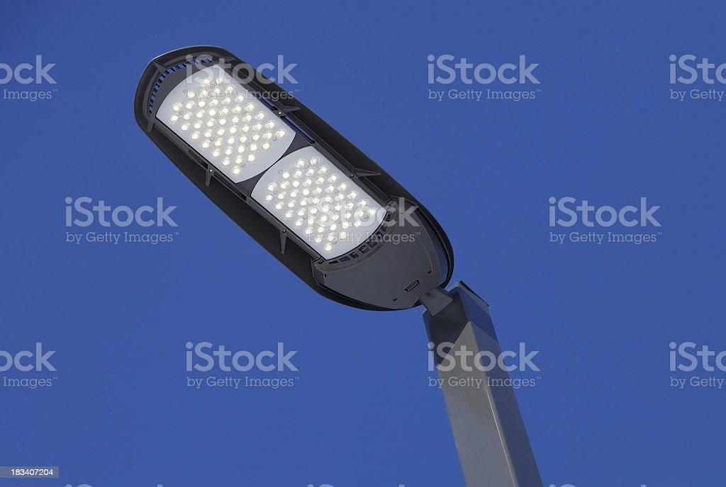 Illuminated LED Streetlight against a Clear Blue Sky stock photo