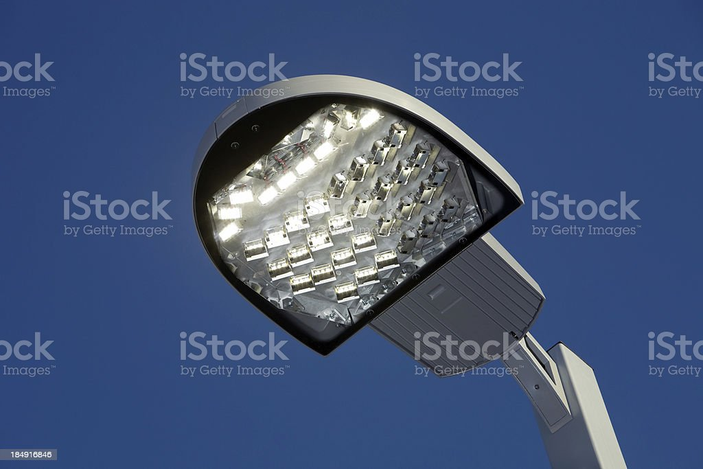 Illuminated LED Streetlight against a Clear Blue Sky stock photo