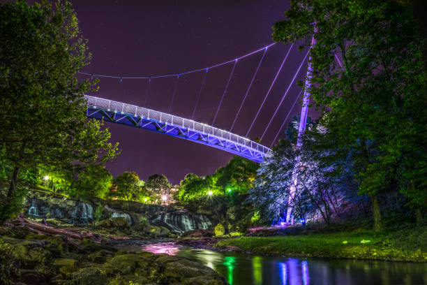 Illuminated Liberty Bridge in Downtown Greenville, South Carolina Illuminated Liberty Bridge in Downtown Greenville, South Carolina SC taken from the Reedy River. liberty bridge budapest stock pictures, royalty-free photos & images