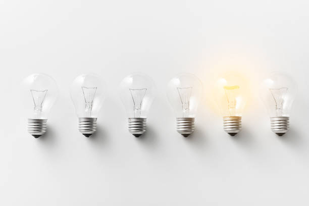 illuminated light bulb in row of dim ones - light bulb stock pictures, royalty-free photos & images