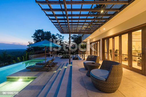 Early morning sunrise at a luxurious villa with a magnificent swimming pool and armchairs. The property is fully illuminated and contrasts with the dark blue sky at dawn. The villa is situated in Uluwatu in Bali