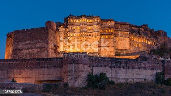 Panorama of illuminated majestic Mehrangarh Fort at twilight after sunset under blue cloudless sky. Jodhpur, Rajasthan, India.