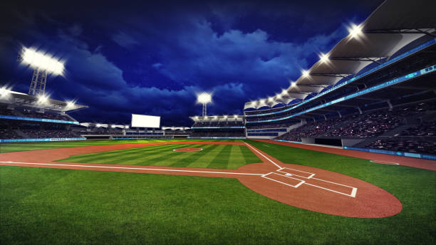 illuminated modern baseball stadium with spectators and green grass stock photo