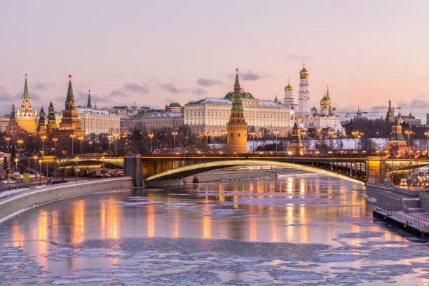 Illuminated Moscow Kremlin and Moscow river in winter morning. Pinkish and golden sky with clouds. Russia Illuminated Moscow Kremlin and Moscow river in winter morning. Pinkish and golden sky with clouds. Russia moscow russia stock pictures, royalty-free photos & images