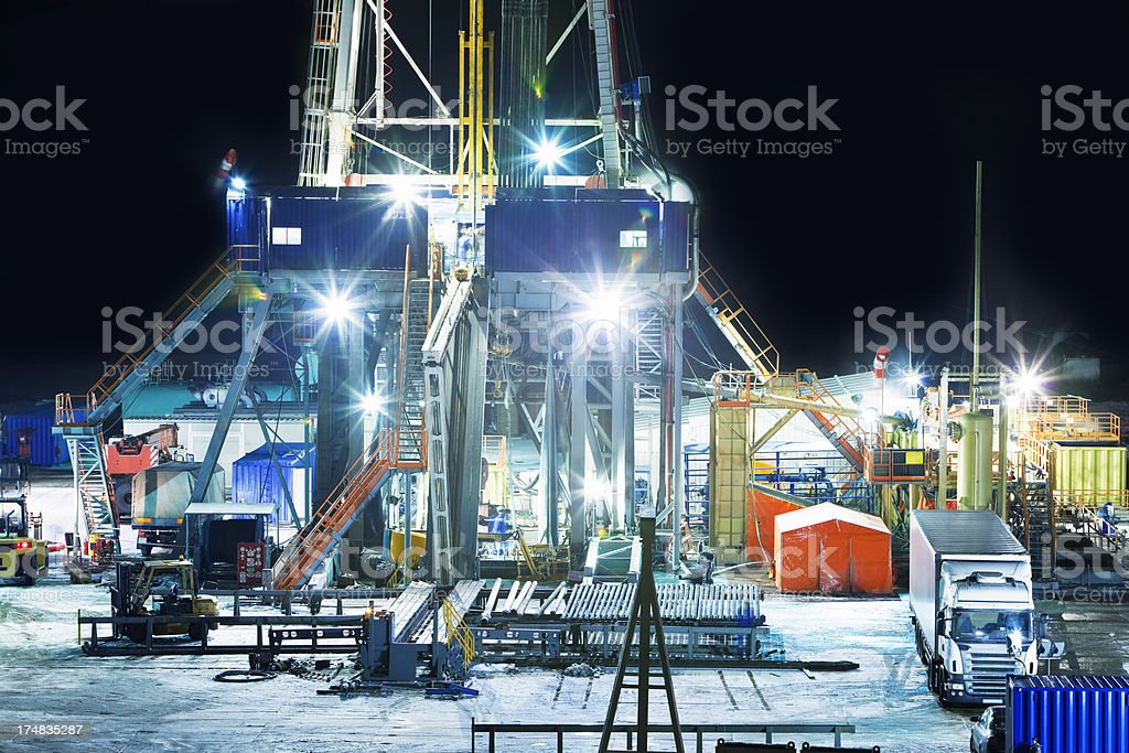 Illuminated Oil Drilling Tower at Night stock photo