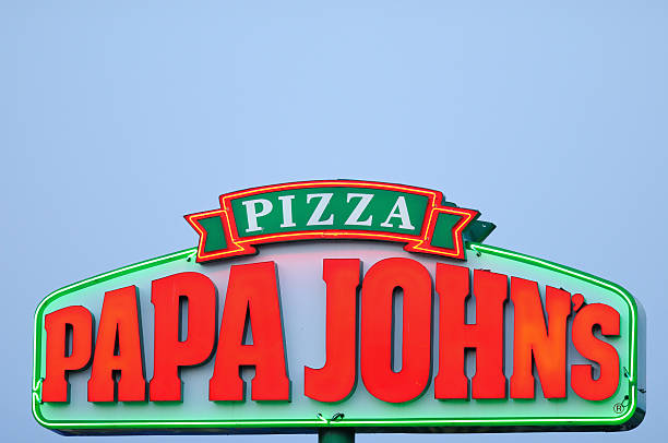 Illuminated Papa John's Pizza Sign at Sunset stock photo