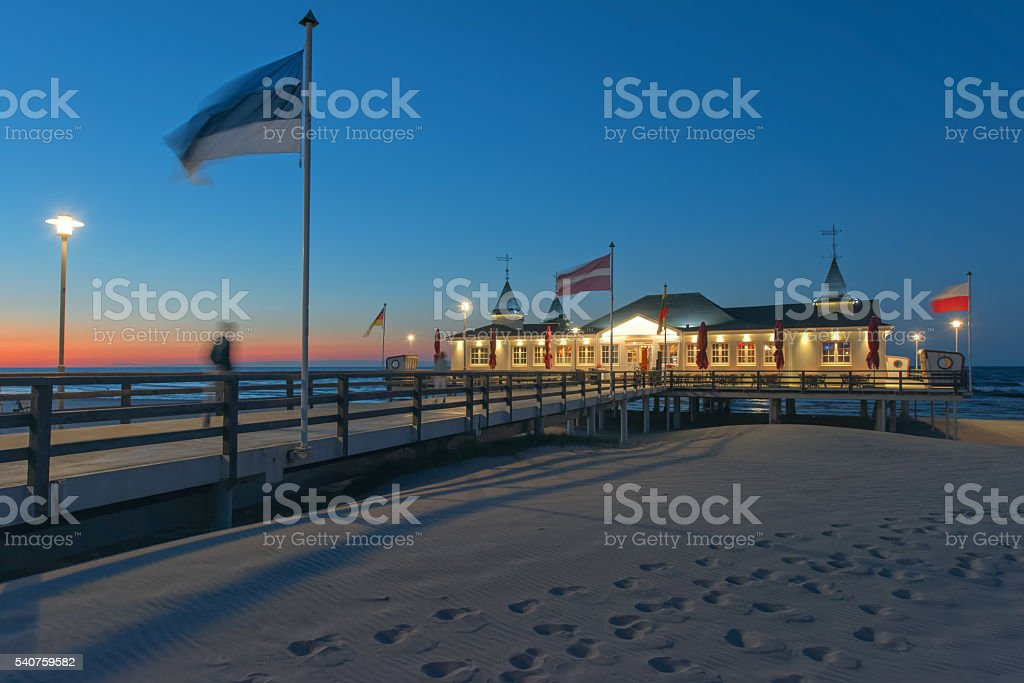 Illuminated pier on sand coast at dusk stock photo