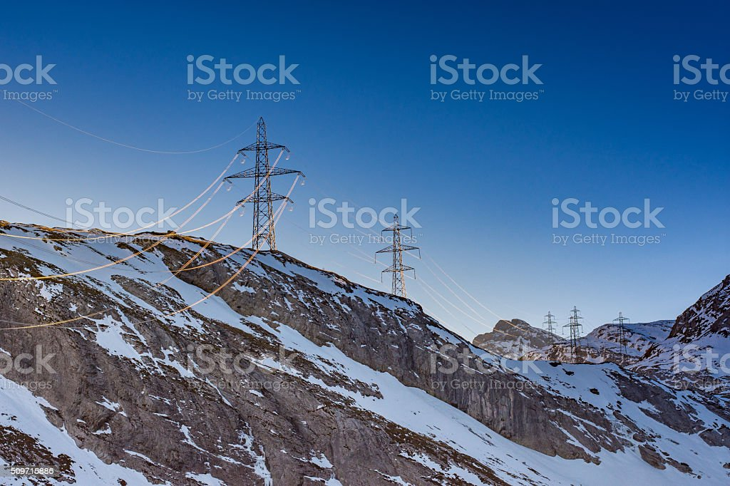 Illuminated Power Power lines late afternoon close to Schwarenbach, Kandersteg, Switzerland. Cable Stock Photo