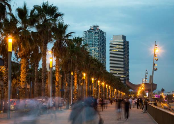 Muelle iluminado en Barcelona con gente borrosa - foto de stock