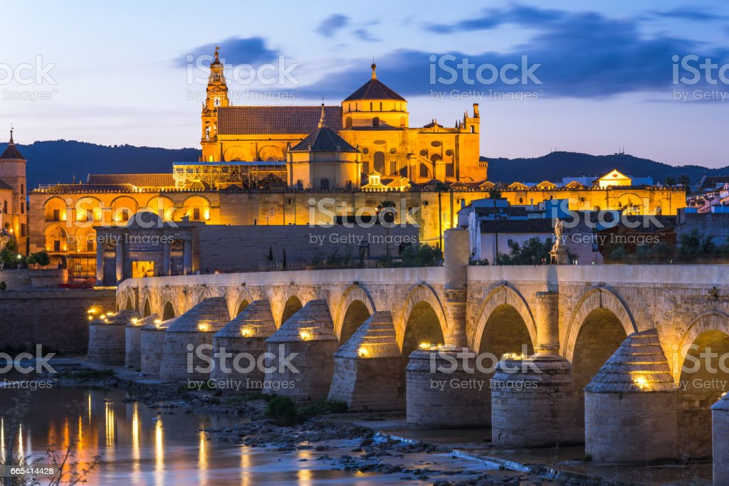 Illuminated Roman Bridge and Mosque-Cathedral at twilight in Cordoba, Spain stock photo