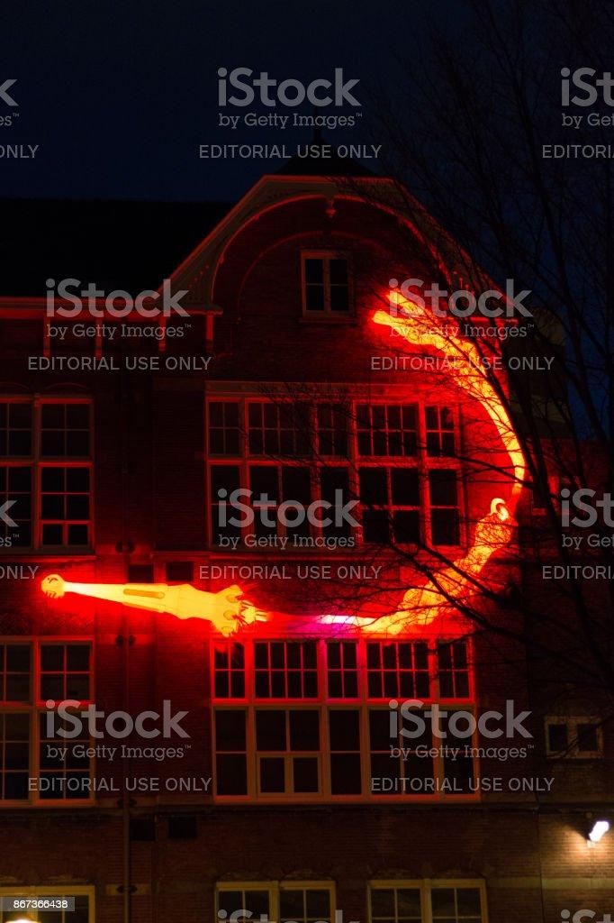 Illuminated rotifers on a wall by night at Amsterdam Light Festival stock photo