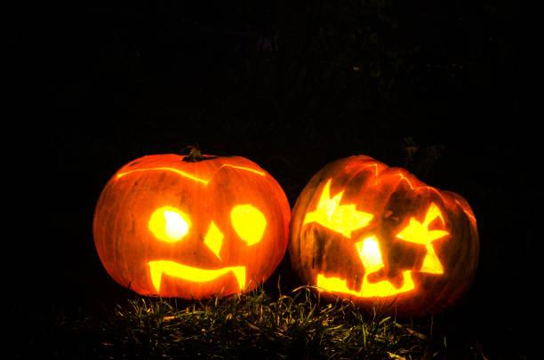 illuminated scary halloween pumpkins shining in dark night