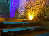 Castelldefels, provincia de Barcelona, España, 24/07/2020. Detalle de una escaleras a una zona de paso del complejo arquitectónico del castillo de Castelldefels. El castillo data del año 967 dC, pero tal como está hoy fue construido en gran parte en el siglo XVI. En 1897, Manuel Girona compró y rehabilitó el castillo. Finalmente, en 1988 fue adquirido por el Ayuntamiento de Castelldefels y comenzó su proceso de recuperación hasta hoy, en el que ya se han restaurado sus salas y espacios principales y donde se celebran diversos eventos que forman parte de la vida de la ciudad. En la imagen, perspectiva abstracta sobre detalle de las escaleras de una zona de paso. Fachada de ladrillo y piedra erosionada por el tiempo y parcialmente reconstruida. Luz amarilla que ilumina la fachada desde el suelo. Iluminación de parte de la fachada con reflejos de luz en tonos naranja, violeta, azul y verde. Reflejos de luz turquesa en las escaleras.