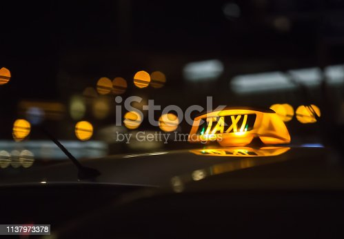 illuminated sign taxi on the roof of the car at night