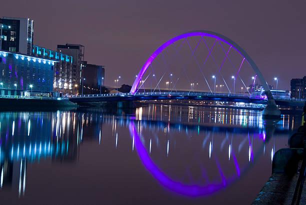 Illuminated Squinty Bridge crossing the River Clyde, Glasgow, Scotland. stock photo