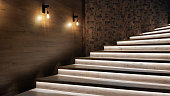 istock Illuminated staircase with wooden steps and illuminated at night in the interior of a large house 1248690144