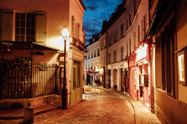 illuminated streets of monmartre quarter, street in paris at night - paris france stock photos and pictures