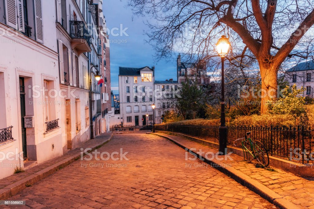 Illuminated streets of Monmartre quarter, street in Paris at night stock photo