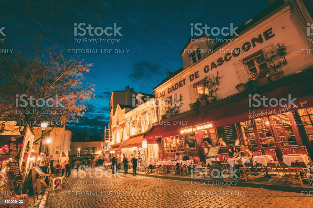 Illuminated streets of Monmartre, street in Paris at night stock photo