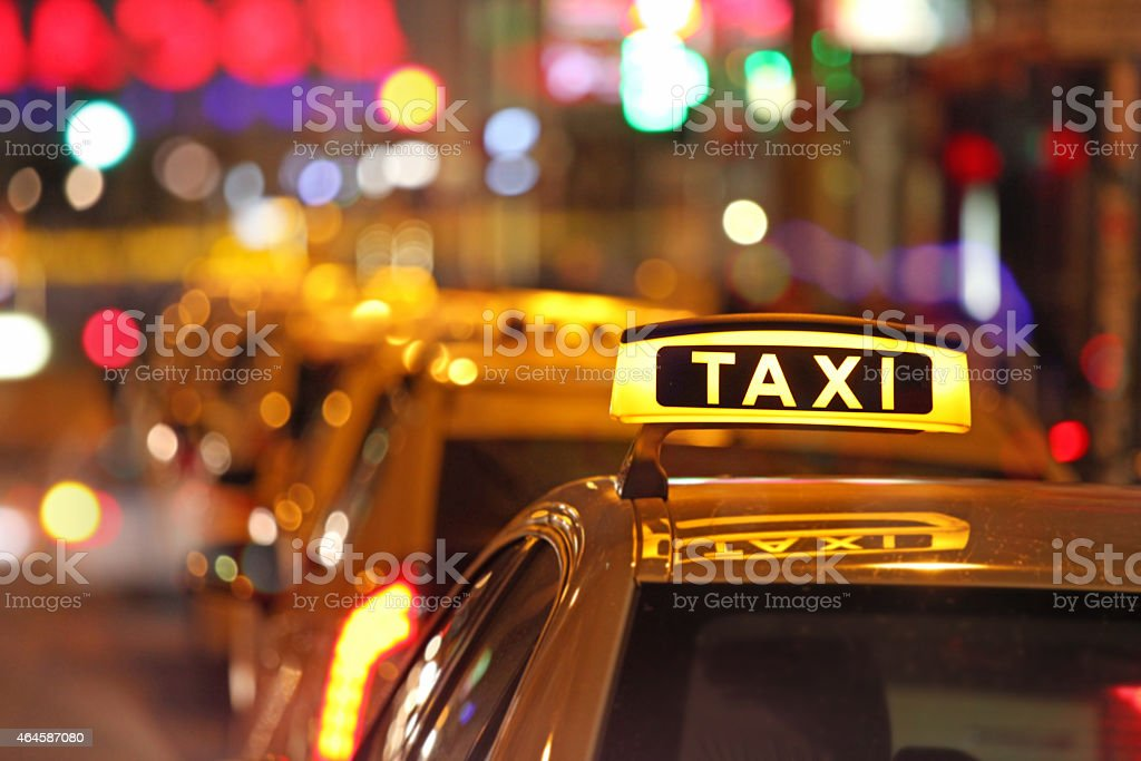 Illuminated taxi sign and city traffic, cars waiting in line stock photo