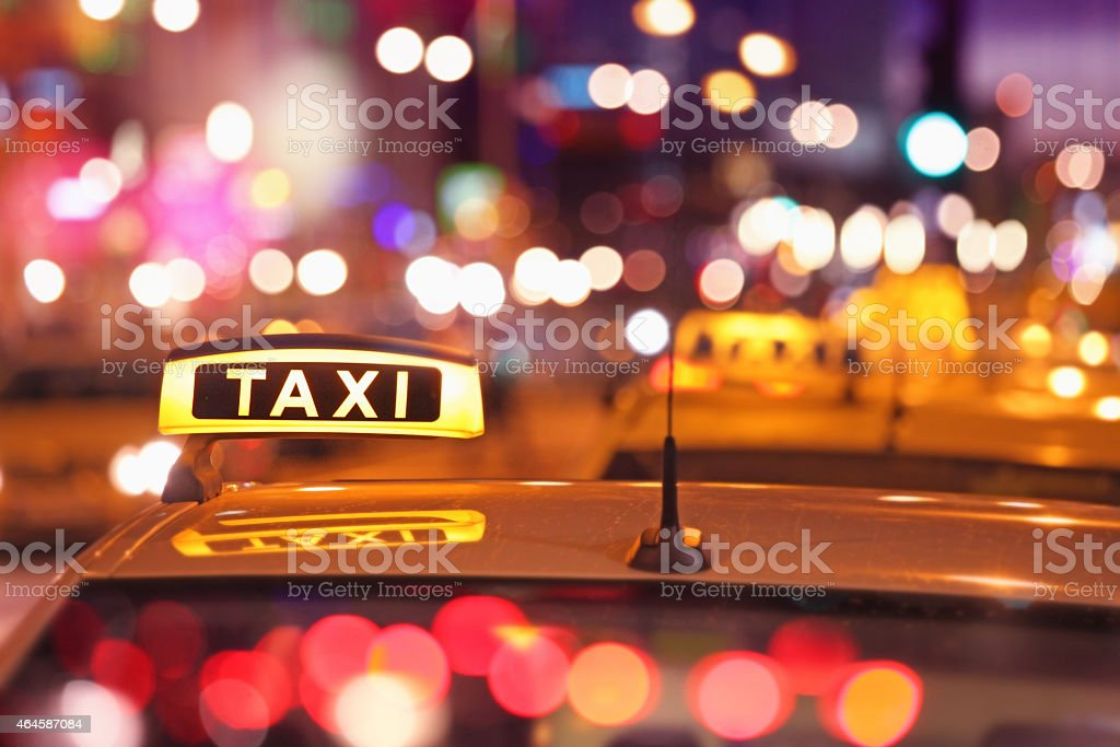 Illuminated taxi sign at night, cars waiting in light stock photo