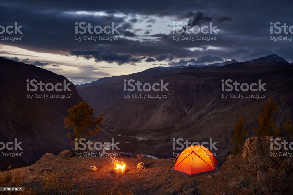 A illuminated tent and campfire in mountains in dawn stock photo