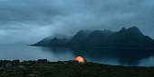 Illuminated tent at the lofoten islands on the rainy evening with copy space