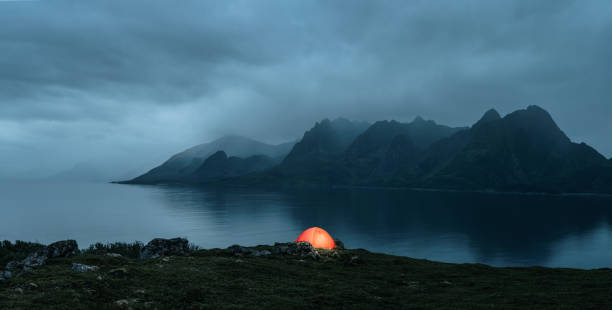Illuminated tent at the lofoten islands Illuminated tent at the lofoten islands on the rainy evening with copy space lofoten stock pictures, royalty-free photos & images