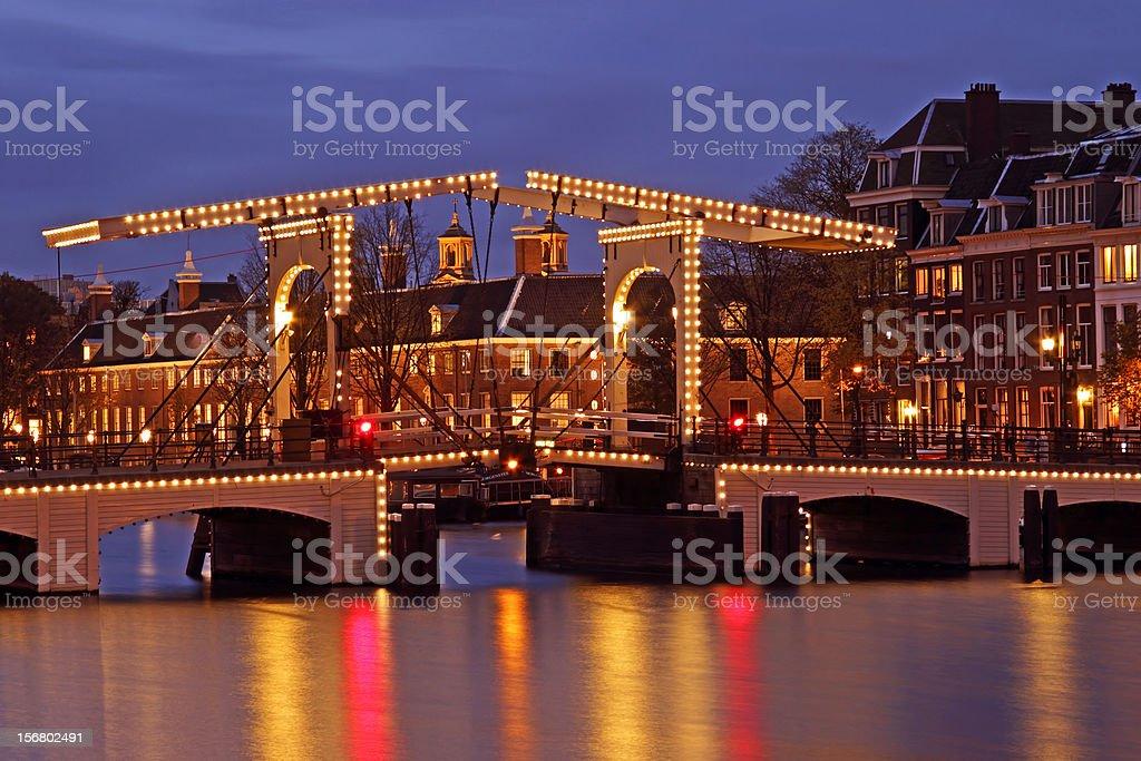 Illuminated Thiny bridge in Amsterdam the Netherlands at twiligh stock photo