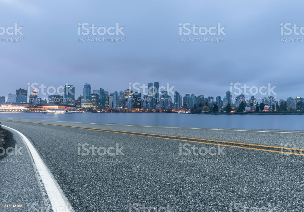 illuminated vancouver downtown skyline with empty highway on foreground stock photo
