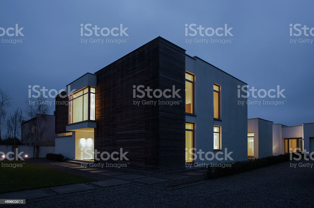 Illuminated windows in detached house stock photo