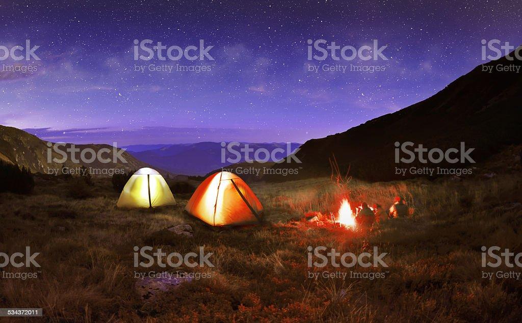 Illuminated yellow camping tent under stars at night stock photo