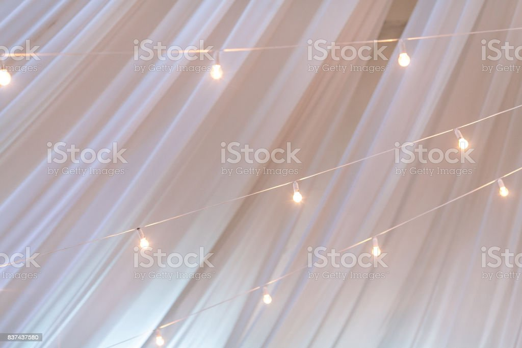 illumination, decoration, celebration concept. against the background of white ghostly transparent curtains there are lots of turned on light bulbs that decorating space stock photo