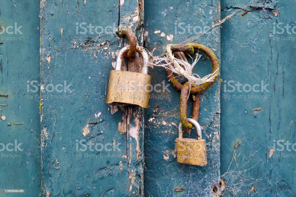 Illusion of safety Two padlocks locking nothing on a door giving an illusion of safety. Ancient Stock Photo