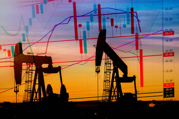 Illustration depicting the historic fall in the price of oil with an oil well in silhouette in the background stock photo
