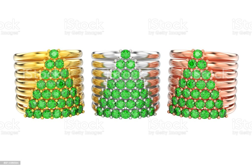 3D illustration isolated three different gold decorative diamond rings with green emerald diamonds in the form of a сhristmas tree stock photo