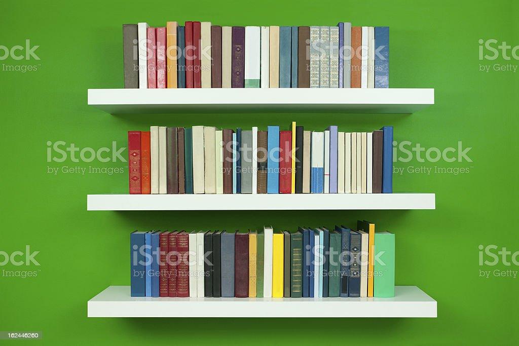 Illustration of full white bookshelves on a green wall stock photo