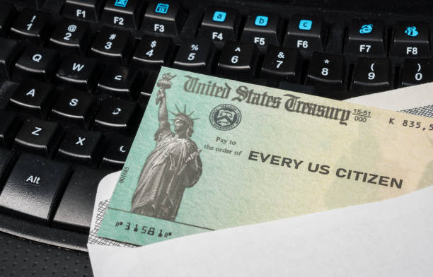 Illustration of the federal stimulus payment check from the IRS on keyboard US Treasury concept check to illustrate coronavirus stimulus payment on keyboard used for working from home stimulus check stock pictures, royalty-free photos & images