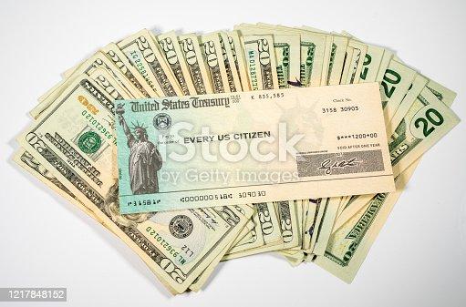Stack of 20 dollar bills with US Treasure illustrative check to illustrate coronavirus stimulus payment on white background