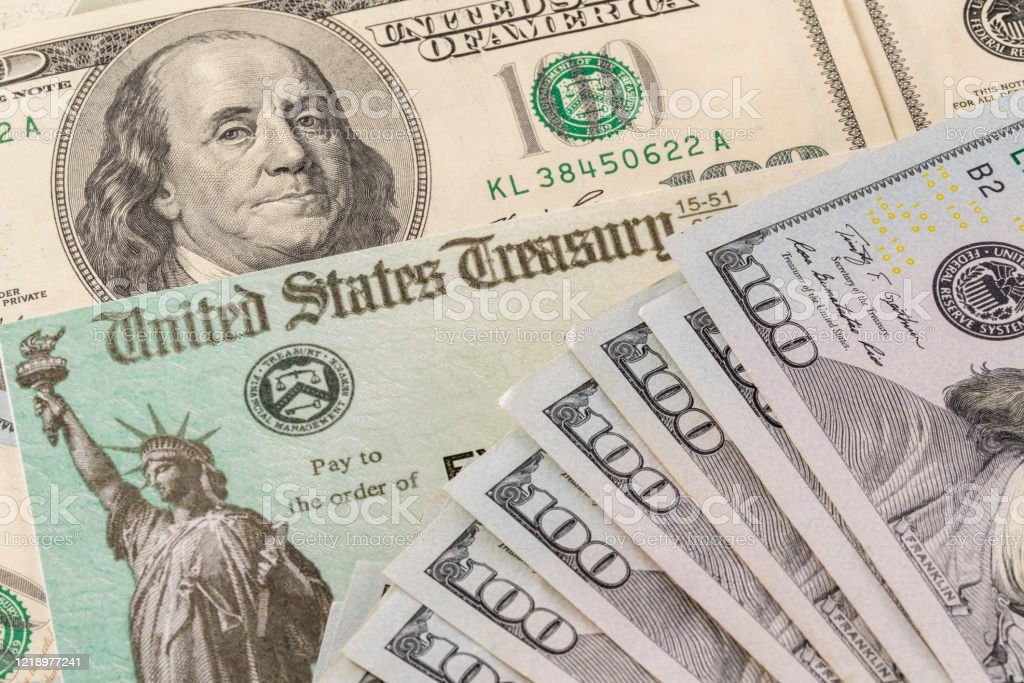 Illustration of the federal stimulus payment check with stack of cash surrounding payment Stack of 100 dollar bills with illustrative coronavirus stimulus payment check to show the virus stimulus payment to Americans American Culture Stock Photo