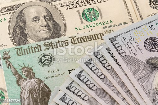 istock Illustration of the federal stimulus payment check with stack of cash surrounding payment 1218977241