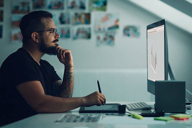 Illustrator At Work. Graphic Illustrator or designer working in his own office. Using digitized graphic tablet, drawing with digitized pen. Working late. Side view. illustrator stock pictures, royalty-free photos & images