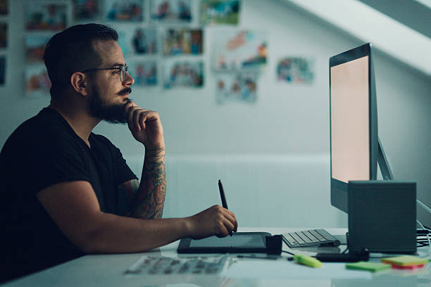Illustrator At Work. Graphic Illustrator or designer working in his own office. Using digitized graphic tablet, drawing with digitized pen. Working late. Side view. White screen so you can add your own project on monitor. illustrator stock pictures, royalty-free photos & images