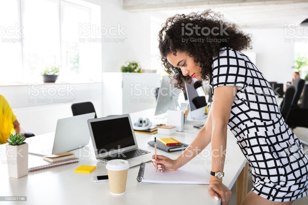 Illustrator sketching new designs in notepad Design professional creating new drawing on notepad. Female illustrator sketching on a book while standing at her work desk. Adult Stock Photo