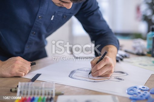 A free lance illustrator sketches out prototypes for an idea onto paper. He is left-handed and using a pen. There are various pens, papers, and art supplies setting on the desk. The shot is focused on the sketch and includes his hand up to mid-chest.
