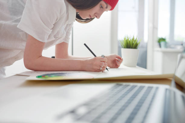 Illustrator working on sketches Young female illustrator working on sketches at home office illustrator stock pictures, royalty-free photos & images