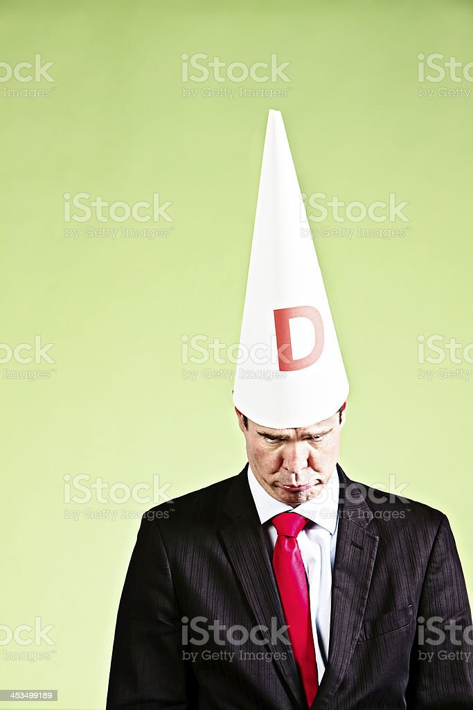 Im sorry! Pouting ashamed businessman in dunce cap stock photo