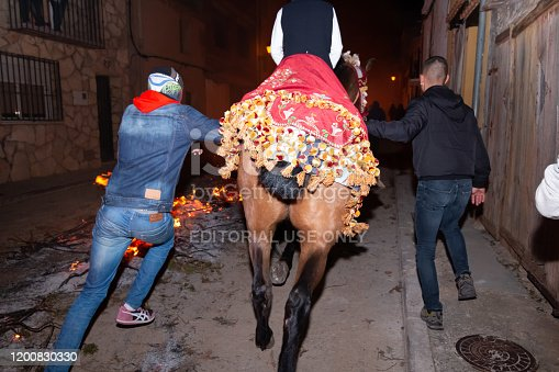 Vilanova d'Alcolea, Castellón, Spain - January 19, 2019: Image behind a horsewoman on a adorned horse with two men accompanying the horse while it´s running in a traditional festivals in Castellon, Spain. Festival concept
