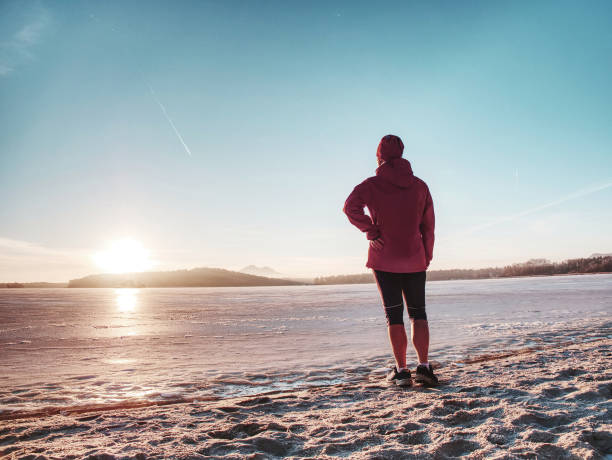 Image from side of athlete woman on beach run in winter stock photo